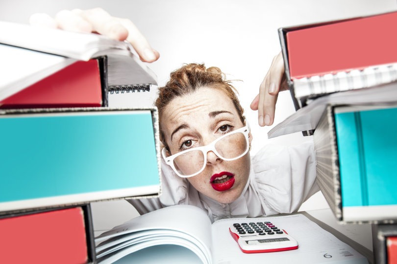 Overwhelmend business owner working on bookkeeping, legal and compliance, and other related tasks