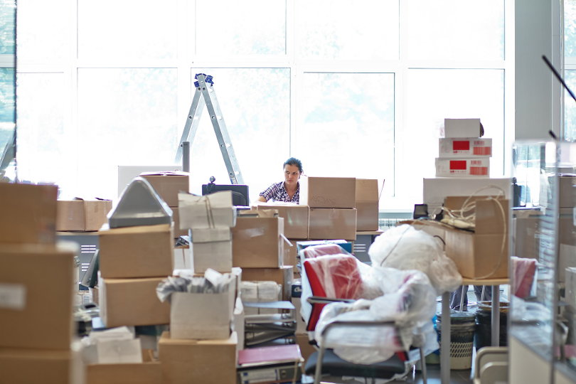 Businesswoman unpacking boxes when moving to a new office